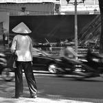 Ho Chi Minh Ville, mutations rapides, rêves de modernité, circulation dense. Sur le bord du trottoir, une femme hésite. Elle semble venir d'ailleurs, d'un monde ralenti, des campagnes vietnamiennes. Cliché : Pascal Clerc